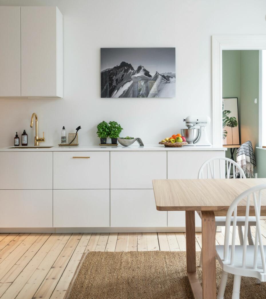 FLYTTE KJØKKEN: Minimalistisk. Kjøkkeninnredningen er fra Ikea. Paret vurderte å videreføre teglsteinsveggene inn på kjøkkenet, men anså dem som for besværlige å holde rene. De gikk i stedet for et mer minimalistisk uttrykk og la på Scotte GT-5 fra Beckers på veggen med sprutsone. Lister, karmer, tak og vegger ellers er malt i klassisk hvit fra Norsjø. Det nye gjesterommet skimtes til høyre. Det har veggfarge Pale Green 8478 Supermatt Pure Color fra Jotun.