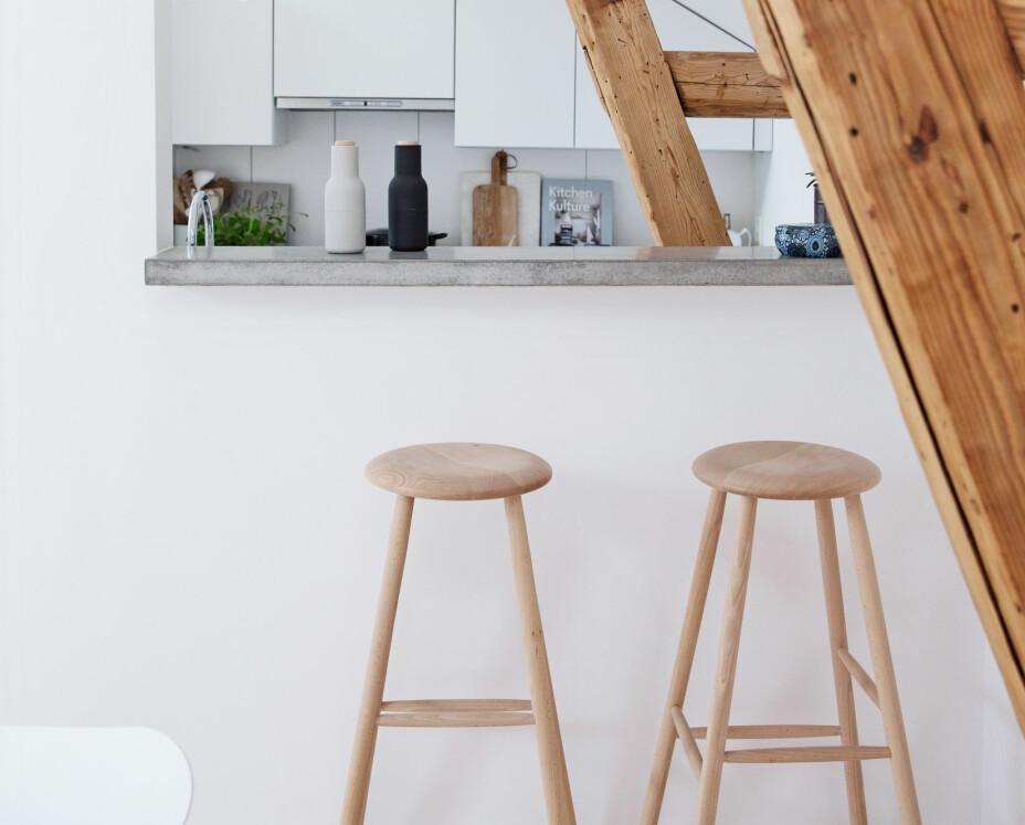 I barområdet står krakker fra et møbelsnekkeri i København. – De er ekstra høye, noe som passer barområdet perfekt, sier Line. Crystal Bulb fra Lee Broom henger over kjøkkensonen. Lyst tre harmonerer utmerket sammen med det hvite interiøret med innslag av betong og røffe bjelker.