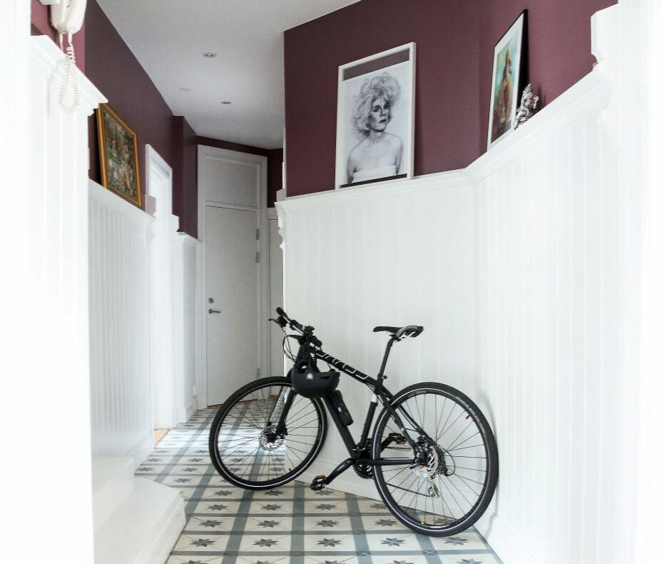 Gulvet i den lange, smale gangen er kledd med historiske fliser, historiske.no. Her er det plass til syklene, og høyden er utnyttet ved å lage en smal hylle med yndlingsbildene, bildet som skimtes best, er signert Andy Warhol. Den dype røde fargen er Dusty Purple fra Jotun.