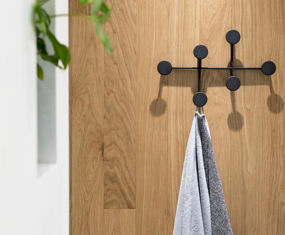 Knaggene Afteroom Coat Hanger i svart er fra Menu. Håndklærne er fra HAY. Parkettveggen hever uttrykket på badet, og gir et snev av stuefølelse til rommet. – Jeg var skeptisk til å ha eik på badet, men i ettertid endte jo den veggen opp med å bli den fineste detaljen, sier Adele.