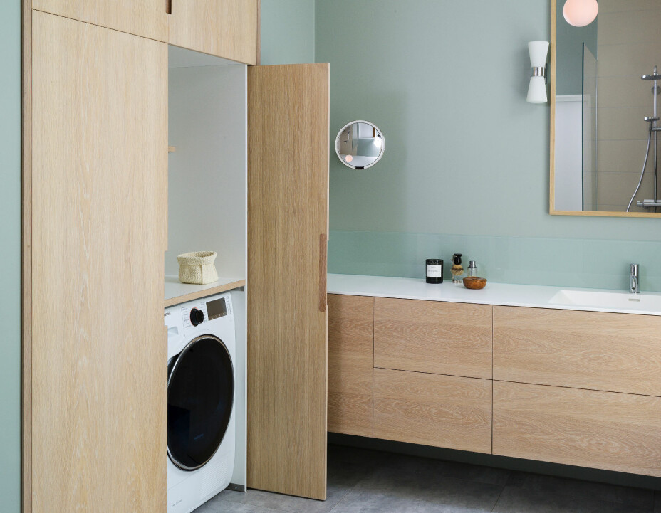 Utfordringen på badet var å få plass til vaskemaskin og tørketrommel, og samtidig ha et delikat og ryddig uttrykk. Løsningen ble å lage skap som skjuler. Pendellampe i himling er levert av SML Lighting på Skøyen.