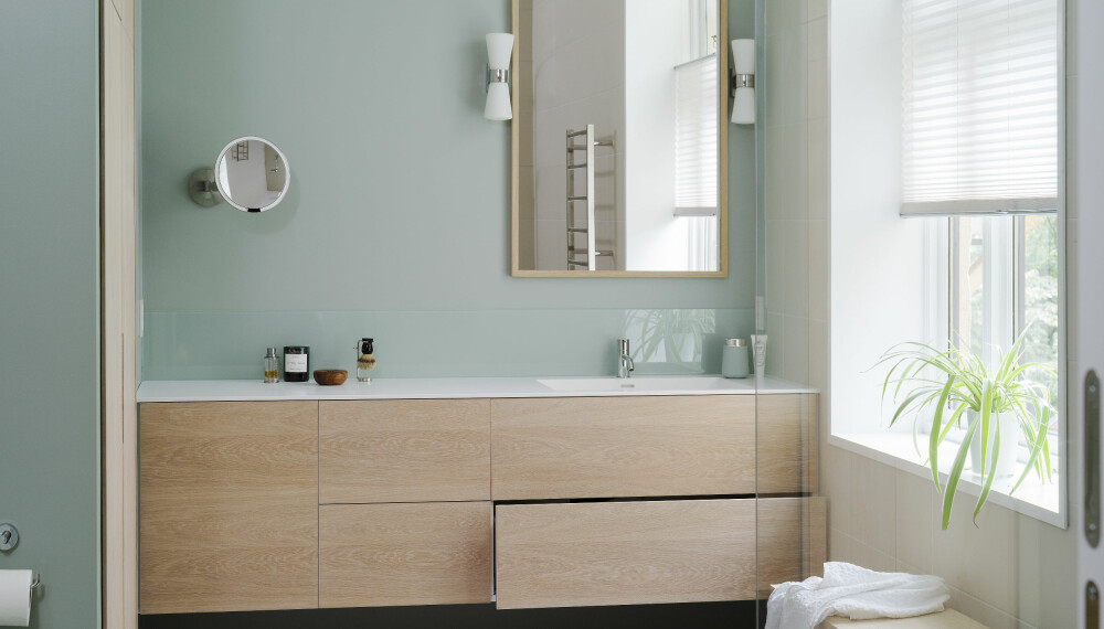 Fargevalget på badet passer godt med eikefiner og bidrar til å gi et art deco-inntrykk. Vaskemaskin og tørketrommel er skjult i skapet til venstre.