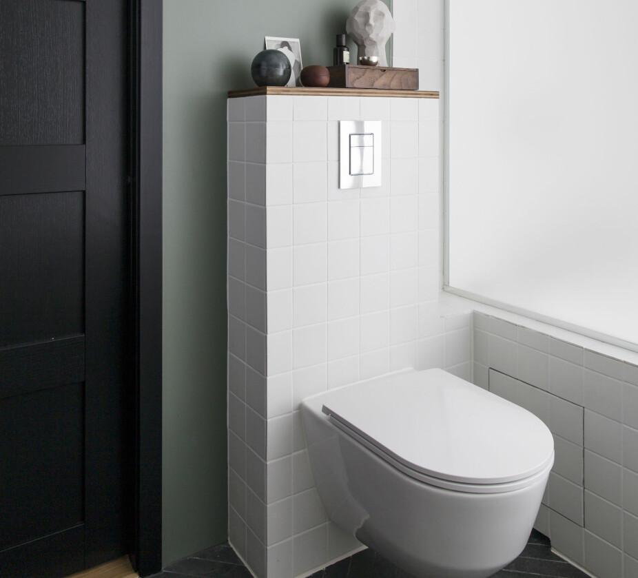 Døren ble flyttet for å få større plass til toalett og badekar langs vindusveggen. Svart dør og listverk er valgt som en kontrast til det hvite og grågrønne. Spesialbygget glassvegg i frostet glass er fra Mesterglass. Toalettet er fra Laufen. Døren er levert av Swedoor.