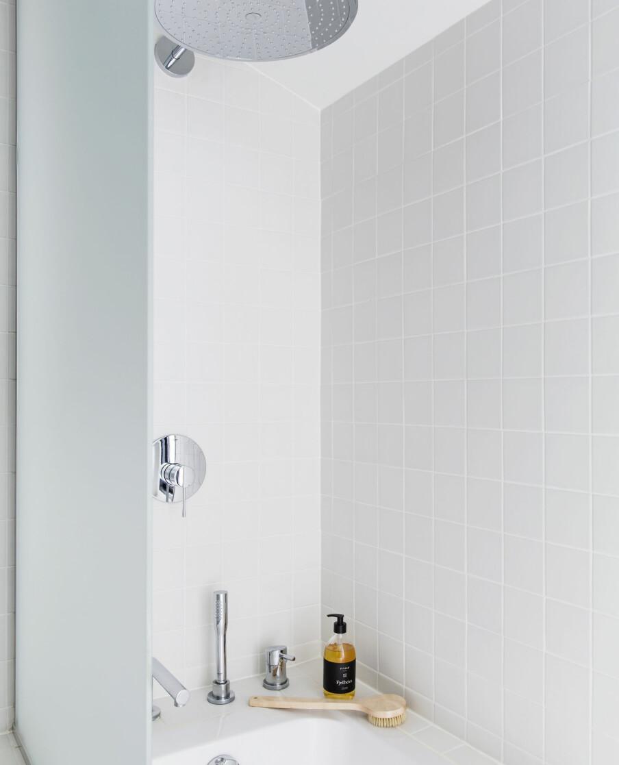 En liten vegg i frostet glass gjør at badekaret også fungerer som dusjhjørne. Skrubbe-børste fra Meraki/Ting, flytende såpe fra Fitjar. Armaturen er fra Grohe.