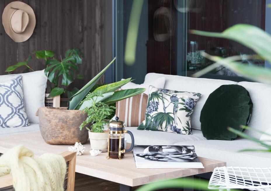 På verandaen trives familien godt i kveldssolen, og her tar de gjerne frem en god bok. Møblene er fra Slettvoll.
