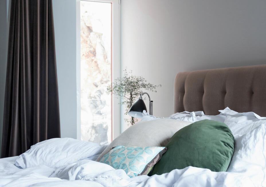 De fargede putene i sengen er fra Mani Studio. Hvitt sengetøy skaper en delikat sommerfølelse. Det avlange vinduet gir utsikt fra sengen, og tykke velurgardiner stenger lyset ute ved behov.