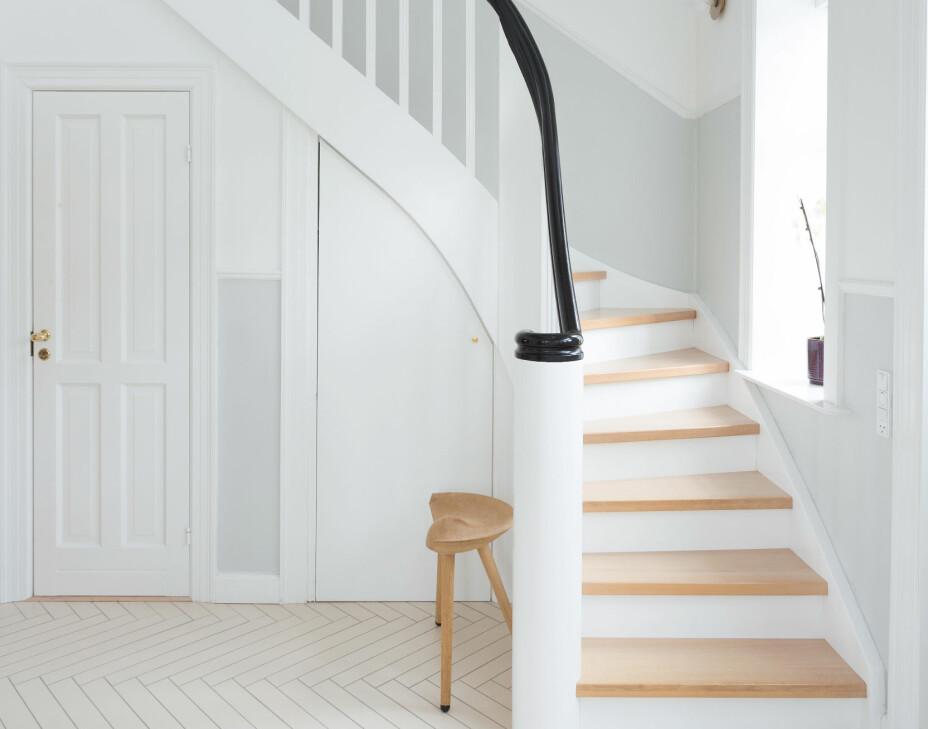 Trappen er plassbygget og formet for å passe til huset stil. Den har en tung, sortmalt håndløper, svungne linjer og nakne trappetrinn i eik, og ser ut som den har stått her siden begynnelsen av forrige århundre. Vegglampene som følger trappen er Liila 1 optic fra Nuura. Gangen er malt i hvitt og en gråblå farge som Nadia har blandet selv av «slanter». – Fargen er fantastisk, dessverre vil jeg aldri kunne gjenskape den, sier Naida. Krakken ML42 fra by Lassen ble designet i 1942 av Nadias oldefar Mogens Lassen.
