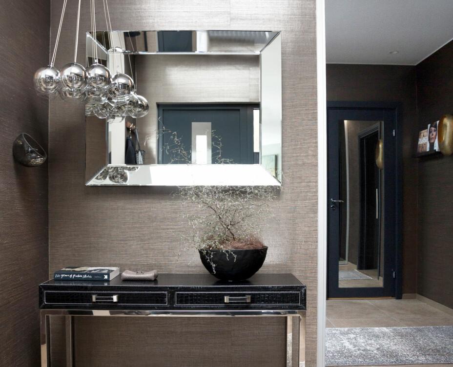 Konsollbordet, speilet og taklampen er alt fra Thomas Hill. Veggskålen til nøkler er fra Bolia og potten med planten er fra Ikea.