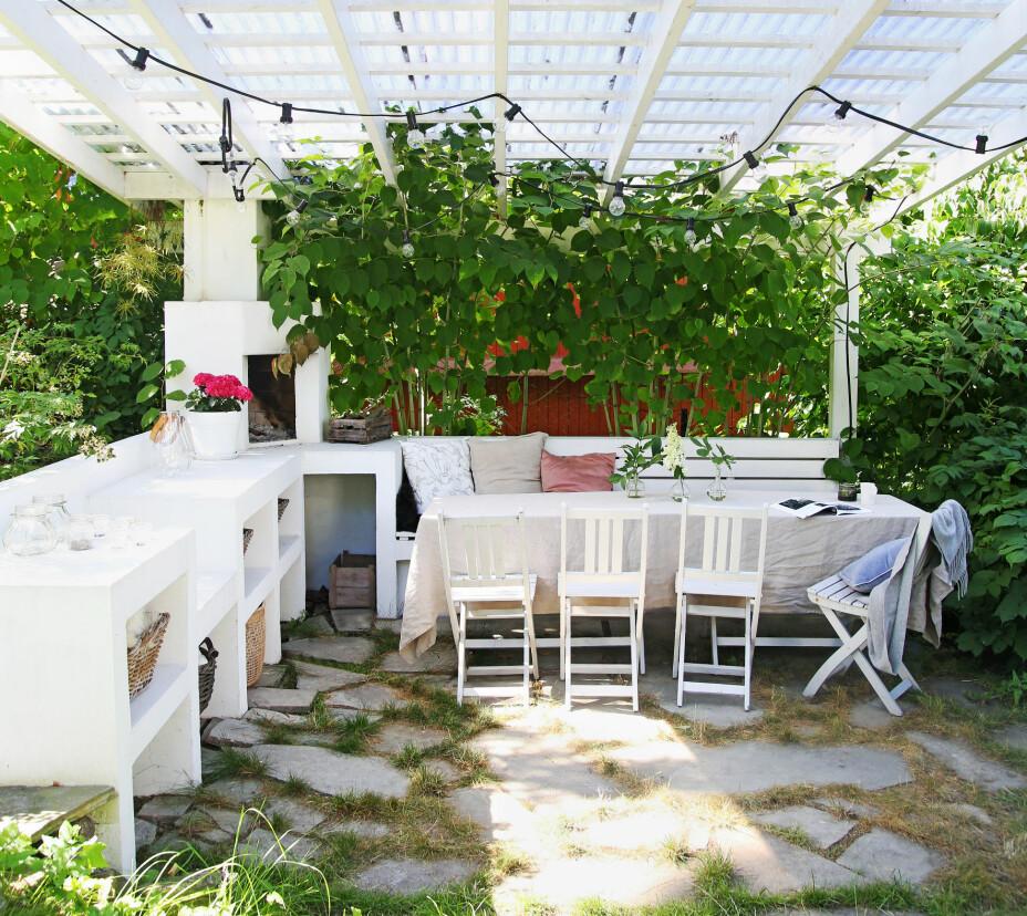 I hagen er det lagt til rette for det gode liv. Her har familien peis, pergola, utekjøkken og en innbydende spisesone.