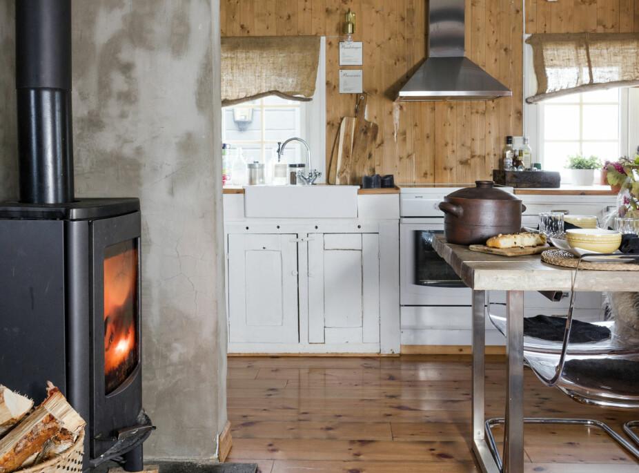 MØBELMIKS: Peisovnen er plassert omtrent midt i hytta, og den varmer godt på kalde dager. Kjøkkeninnredningen i bakgrunnen er en fin miks av gammelt og nytt med møbler som Kai-Robert har snekret selv.