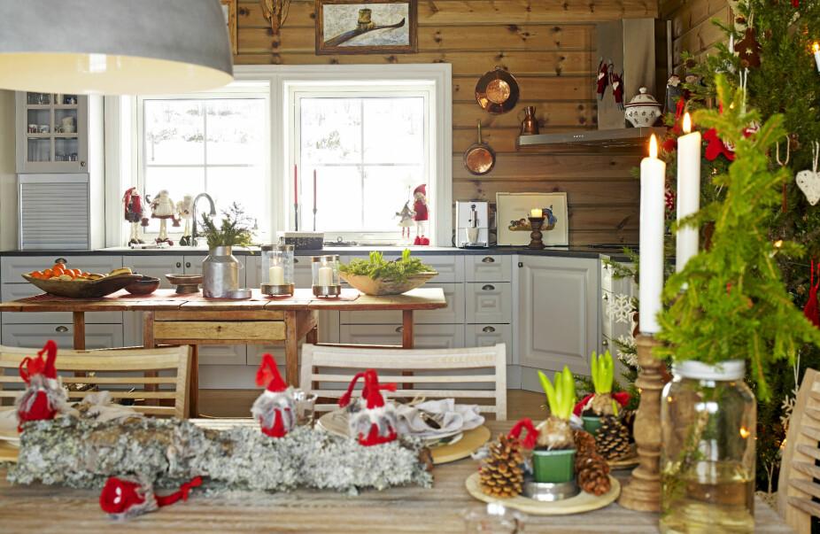 Samlende rom. Kjøkkeninnredningen og spisebordet er plassert i hver sin ende slik at kjøkkenet også har gjennomgang inn til stuen til høyre.