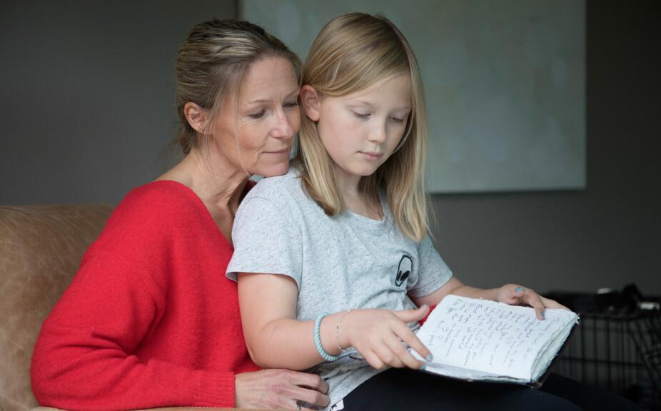 Helene Sandvik kommer med bok om pappa´n sin som ble dement. Her ser hun på notatene fra hennes fra sykdomstiden sammen med datteren Anna (9).