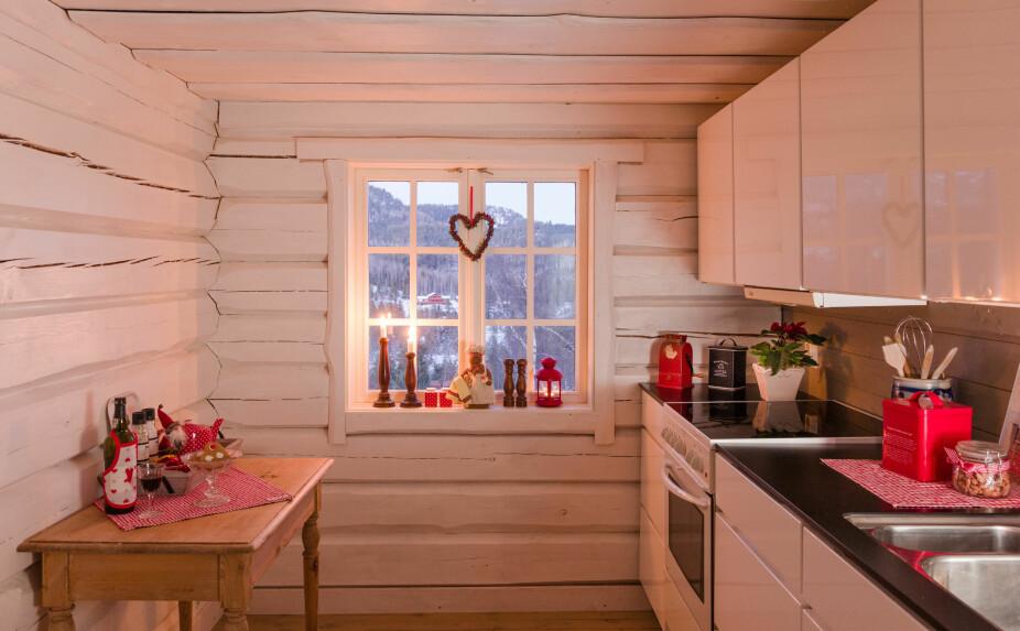 Kine vil ikke henge opp så mye på de flotte tømmerveggene og liker at det er hvite flater på hytta. Litt rød pynt må til i jula.