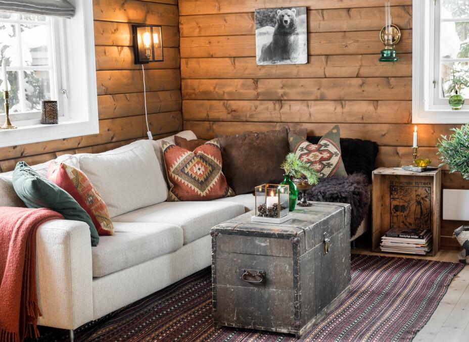 Stuekrok. Bolia-sofaen de hadde hjemme, ble flyttet til hytta. Bordet er en Amerikakoffert de fant på Finn, og kelimteppet kjøpte Richard i Iran for mange år siden.