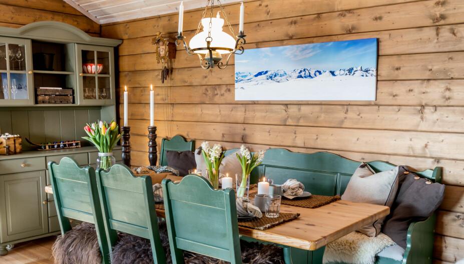 Spiseplass. Spisestuemøblene fulgte hytta, det samme gjorde taklampen. På veggen henger et bilde av Tromsø-fjellene som Richard har fått av søstrene sine.