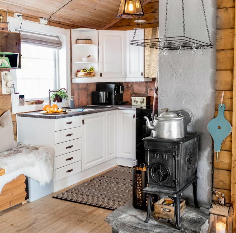 Kjøkkenkrok. Furukjøkkenet ble hvitmalt, de byttet ut hybelkomfyren med en induksjonsovn og satte i tillegg inn et større kjøleskap. Under benken er det en varmtvannsbereder, og kranen er kjøpt på Ebay. Vanntanken er skjult under skinnet ved siden av kjøkkenbenken. Over Jøtul-ovnen har de hengt opp en rist fra Lagerhaus med kjetting og kroker fra Clas Ohlson.