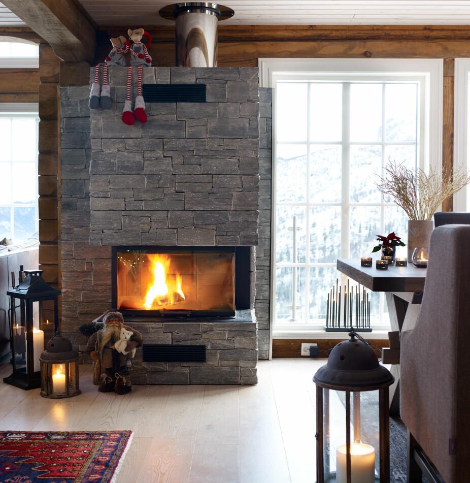 Hyttekos. Joda, det er koselig med peis. Innsatsen fra Rais gjør at bålet kan ses fra gangen, stuen og kjøkkenet. Innsatsen er et kompromiss med ønsket om en grue. Gulvet er 1-stavs eikeparkett, hvitlasert. Taket er hvitbeiset furupanel.