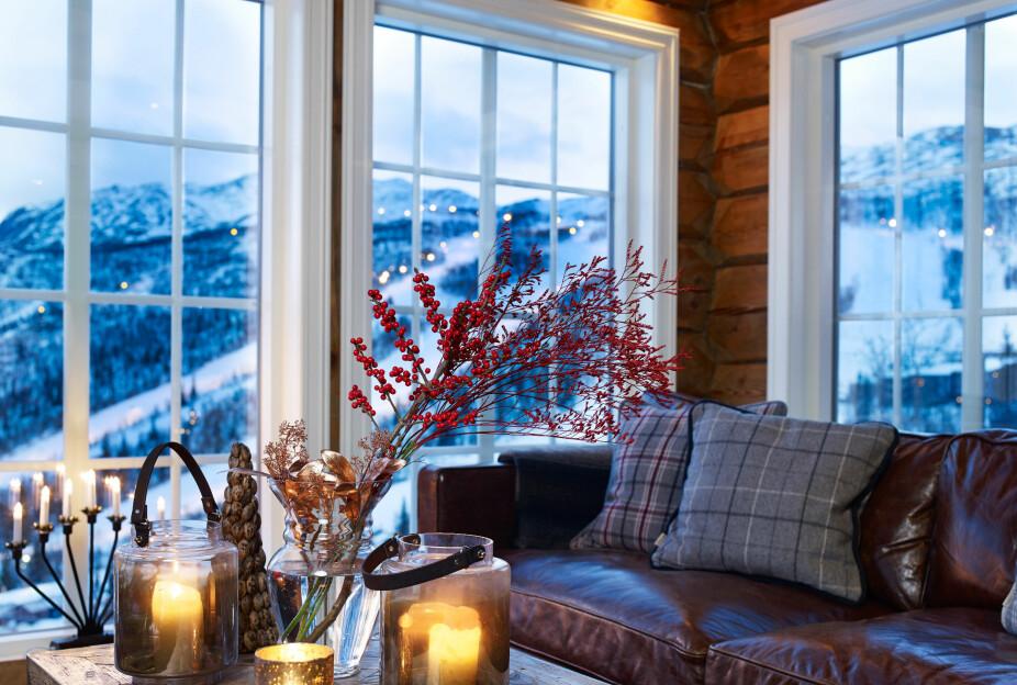 Bergtatt. Paret falt pladask for utsikten mot bakken. Sofakroken er et sted det er godt å være. I blåtimen føles stuen ekstra lun og varm.