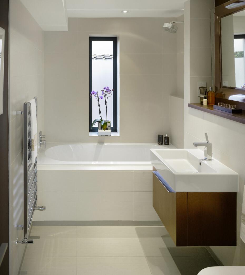 KOMBINERT BADEKAR OG DUSJ: Treverk på badet er in igjen, og sammen med store fliser, downlights og et lite badekar har du er perfekt, lite bad. På dette badet vil badekaret også fungere som dusj.