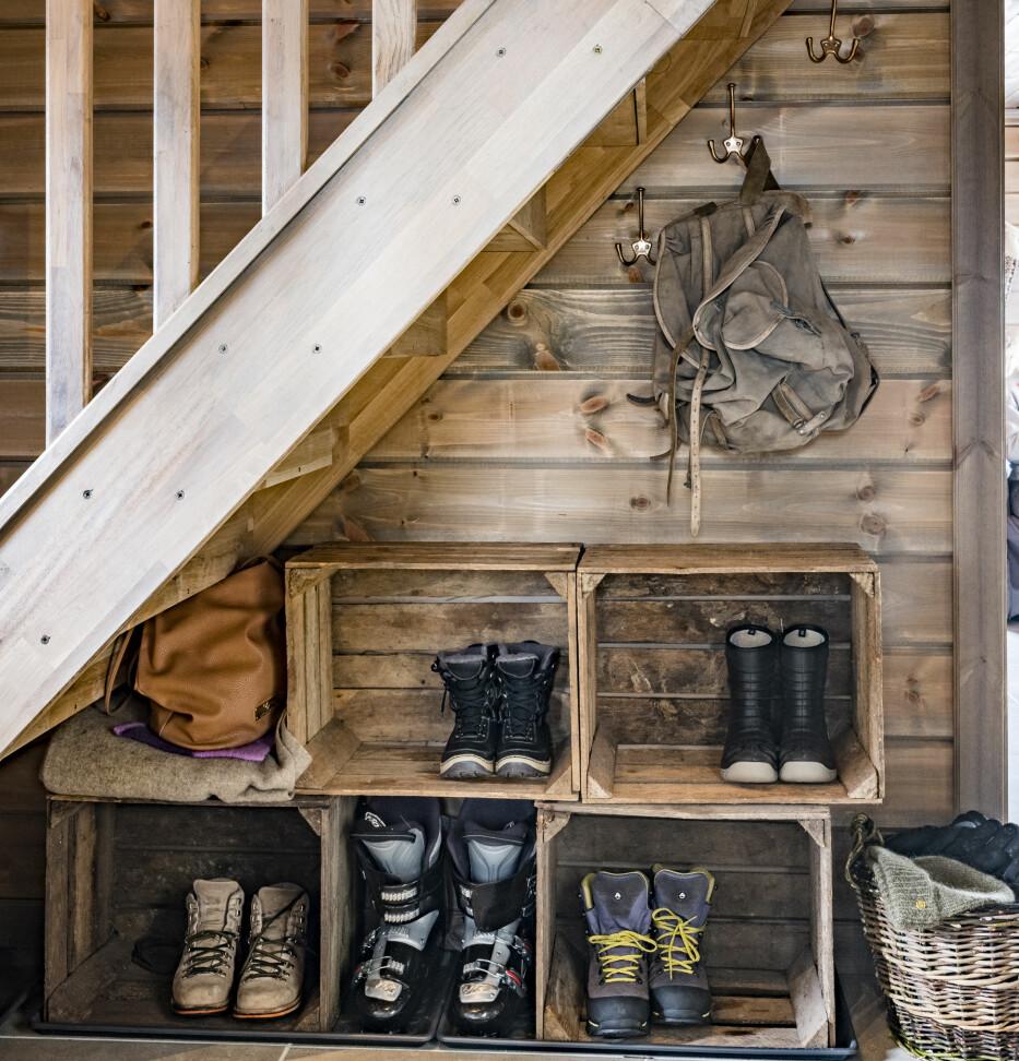 Kassevis Sko flyter som regel rundt i gangen, og  på hytta blir det ekstra mye med ski og slalåmutstyr. Derfor har familien brukt plassen under trappa til å feste flere trekasser sammen. Der er det plass til mange par, og det ser ryddig ut med én gang.
