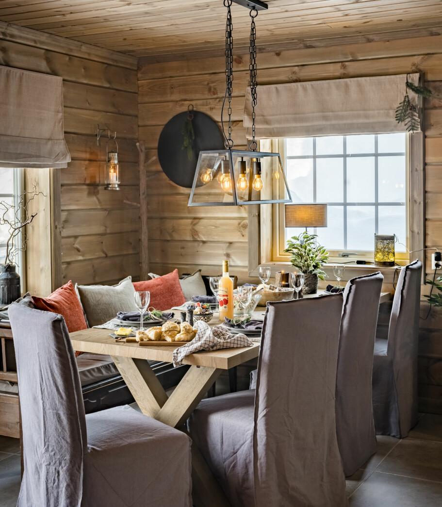 Stilig spiseplass. Bordet er dekket med rustikt servise og tøyservietter. Både sittebenken og stolene er bruktfunn.