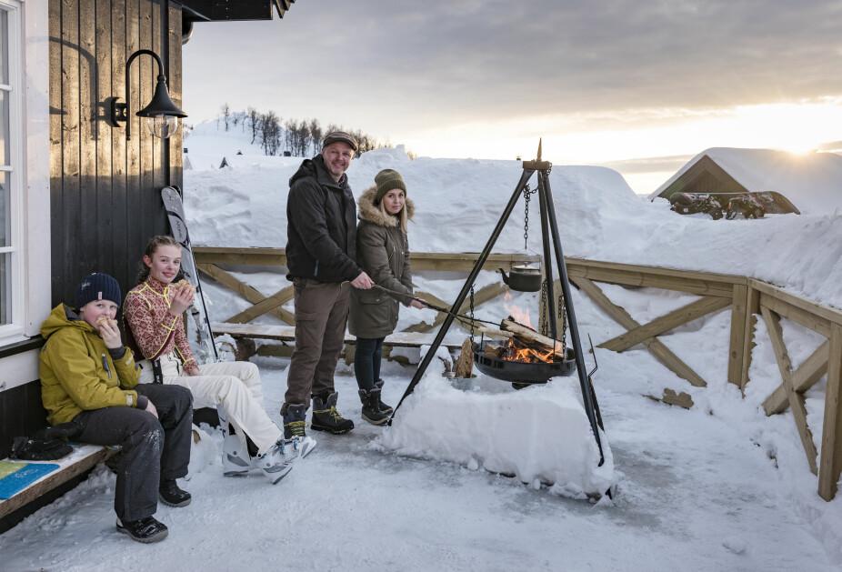 Utekos. Selv om det er veldig mye snø rundt hytta, har familien gravd frem verandaen og laget en koselig plass med bålpanne. Når sola står høyt, er det lunt og godt der.