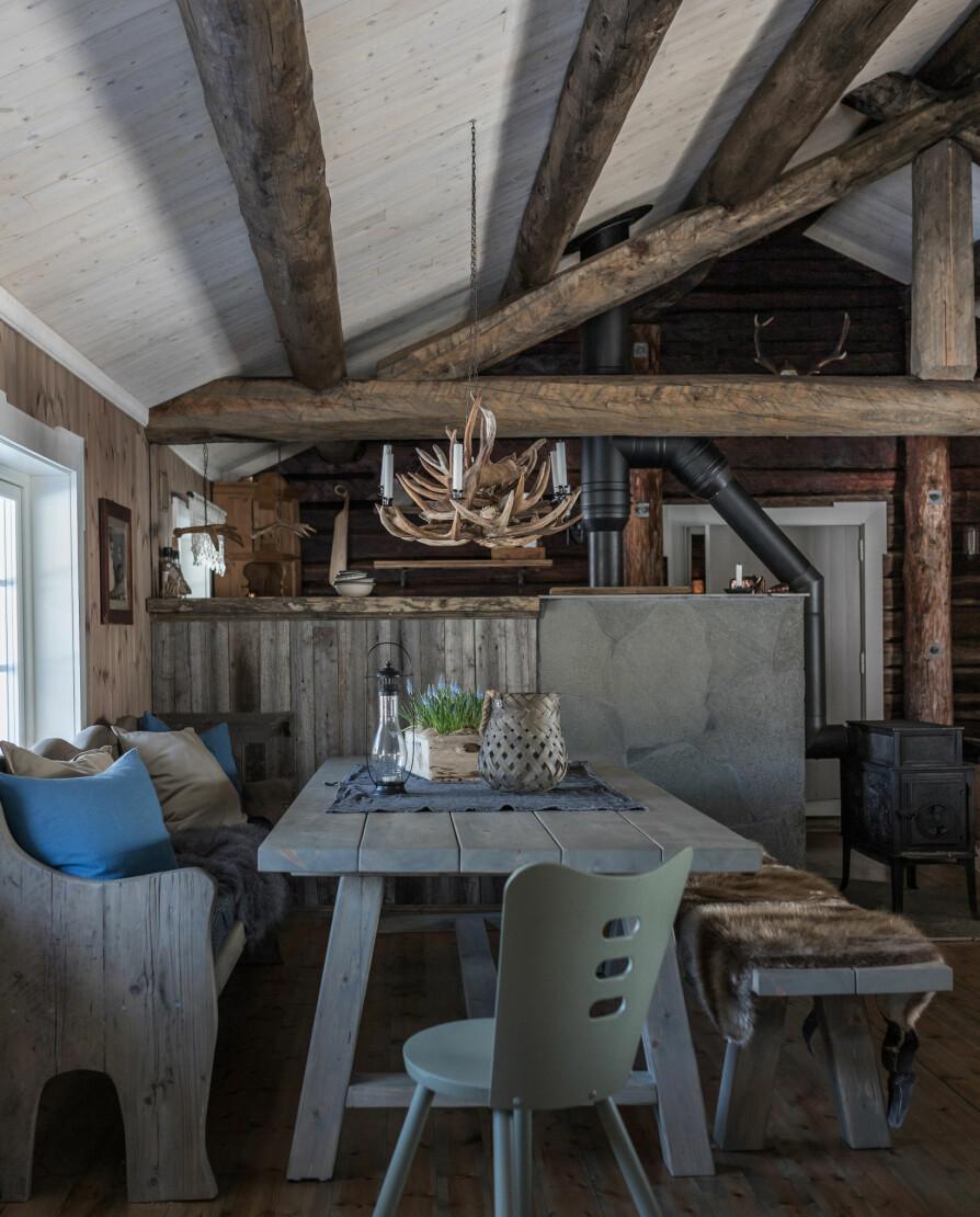 Selvforsynt. Spisebordet og den ene benken har Cathrines far laget, mens den ved vinduet har Thomas bygget av materialer fra en gammel slektsgård, nærmere bestemt gulvet som besteforeldrene til Thomas danset brudevals på. Beverskinnene og taklampen med gevir er fra egen jakt.