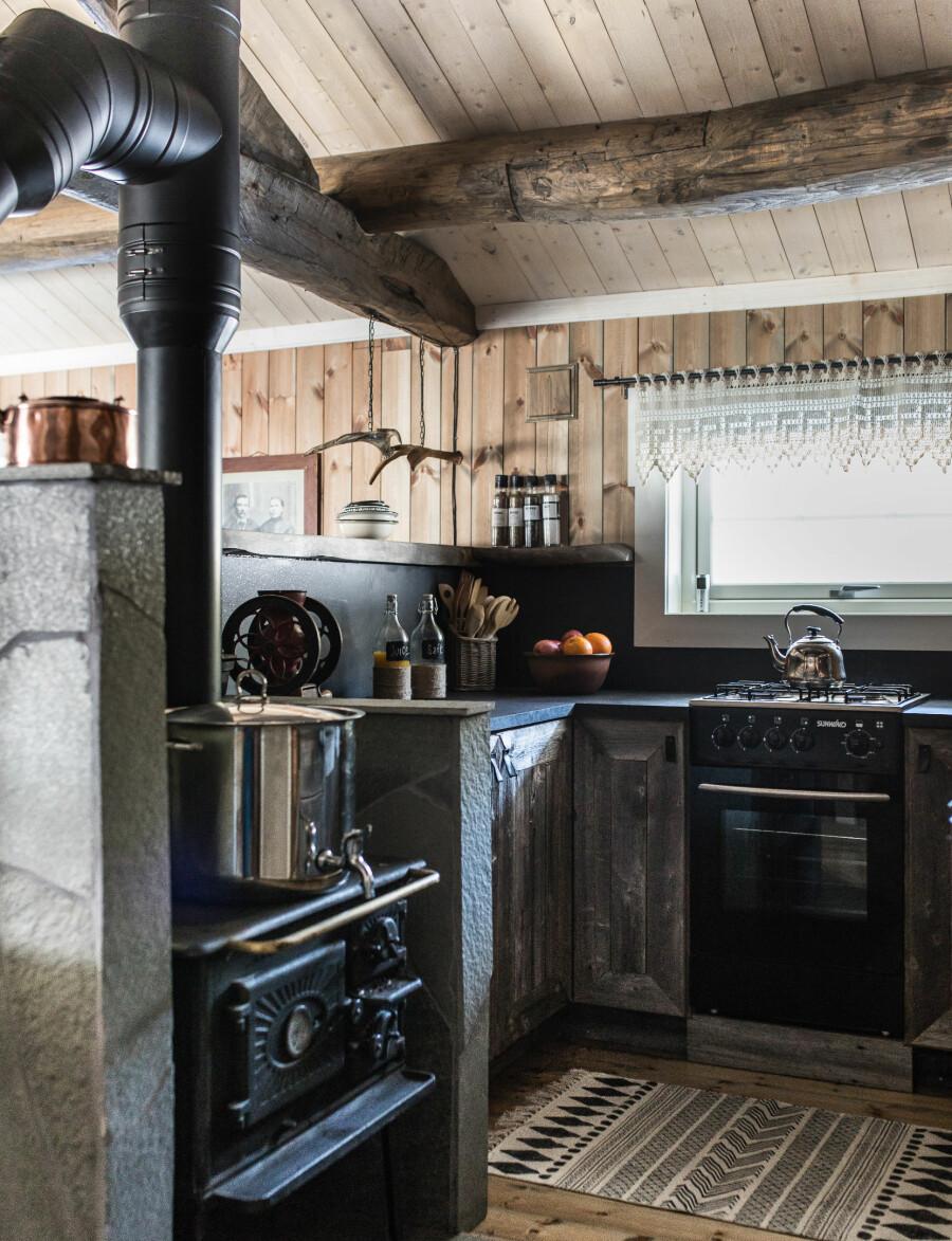 Ung snekkerspire. Eldstesønnen Even er snekkeren bak det fine og stemningsfulle kjøkkenet. Skapene er bygget av materialer  fra et gammelt fjøs i bygda, og den gamle vedkomfyren var en del av designet fra starten. Gardinene er arvegods fra familien.