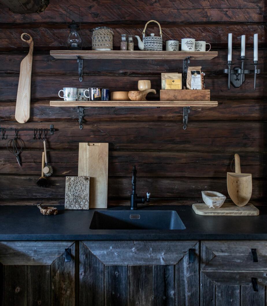 Harmonisk. Den mørke benkeplaten og den sorte kranen fra Ikea passer godt til veggene. Kjøkkenhyllene er laget av gamle gulvbord fra et stabbur.