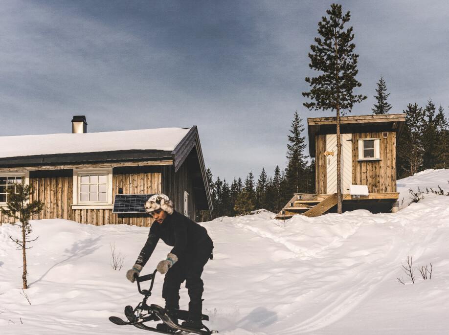 Fartsfull lek. Julian i full fart i en av bakkene foran hytta. Når de drar hjemmefra, spenner han gjerne kjelken bak på snøscooteren og gjør triks underveis.
