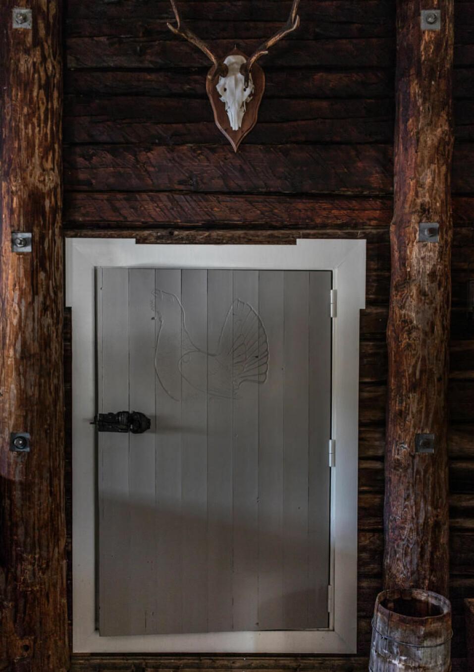 Fjøsdør. Inngangen til den gamle delen av hytta, det opprinnelige fjøset, har fått en lav, bred dør, slik de gamle fjøsene hadde. Thomas har selv bygget  den og skåret motivet av  en tiur i den.