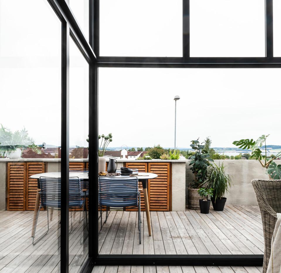 LY: Glassveggene og -taket skjermer for regn og vind, men de slipper også lyset inn og lokker blikket ut. Glassdøren kan skyves til side når man ønsker å åpne opp til den delen av terrassen som ikke er overbygd.