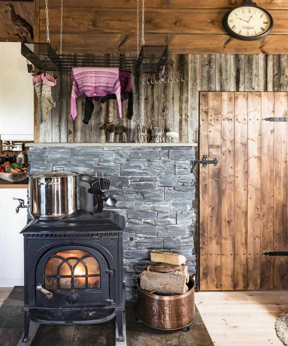 Tørketid Janne er veldig fornøyd med tørkestativet over ovnen. Stativet har hun tegnet og Bård Ove sveiset. Å få tørket våte ullsokker på hytta, er alfa og omega. Veggen i bakgrunnen er laget av gamle materialer fra et fjøs.