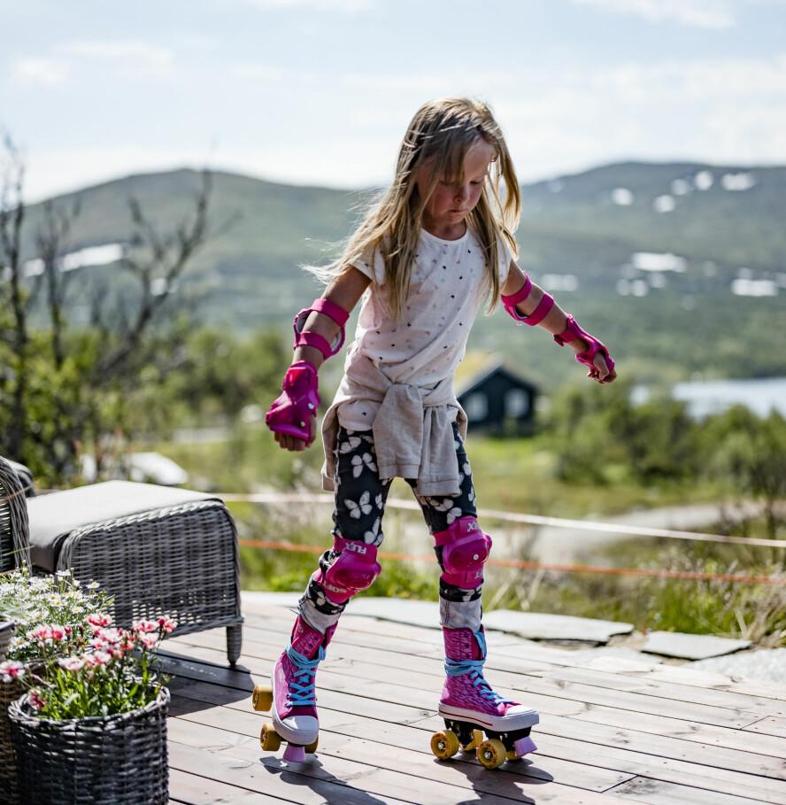 I full aktivitet. De to tvillingjentene er aktive, og de trives både på jakt med pappa og med å leke utenfor hytteveggen.