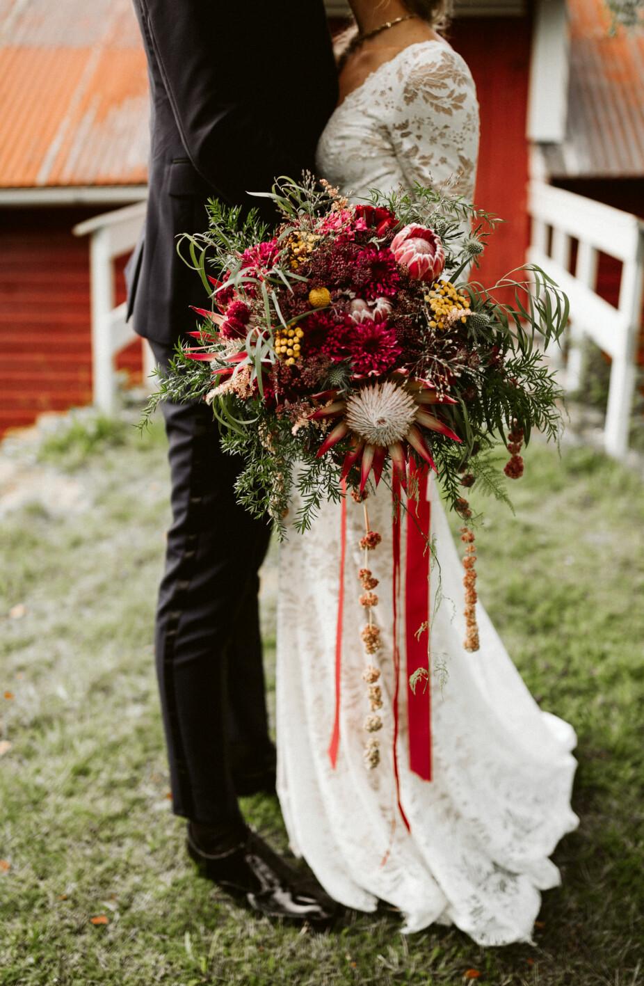Den nydelige brudebuketten, bruden tok selv på røde velur- og silkebånd for det lille ekstra. Protea var den sentrale blomsten i buketten.
