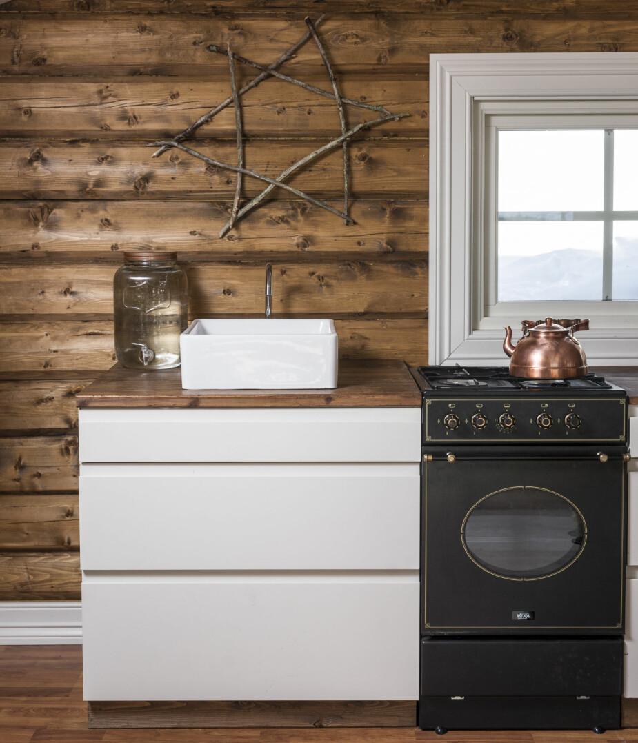Stilrent. Rene, hvite flater mot rustikke vegger gjør kjøkkenet smakfullt og innbydende. Utsikten fra vinduet er upåklagelig, og man kan se rett mot det høye fjellet Veggene.