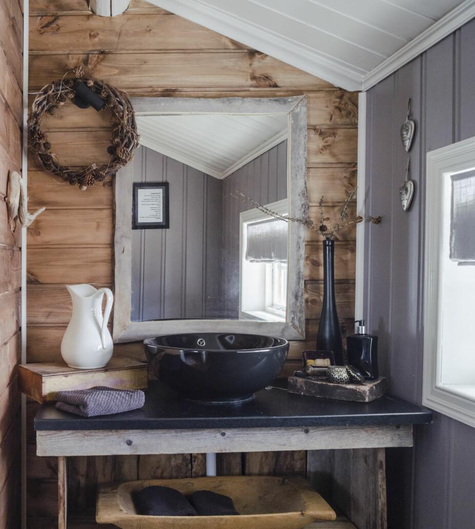 Gjenbruk Badet er rustikt og koselig, og baderomsinnredningen har paret laget selv av gamle materialer, noe som gjør det både unikt og personlig. Badet ligger i den gamle delen av hytta.