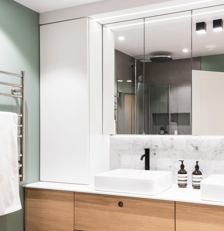 DUSJ: Da badekaret forsvant, kunne innredningen strekke seg fra vegg til vegg. Innredningen er designet av interiørarkitekten, og bygget av møbelsnekker. Takspoter fra Astro Lighting og armaturer fra Vola utgjør rommets svarte aksenter.