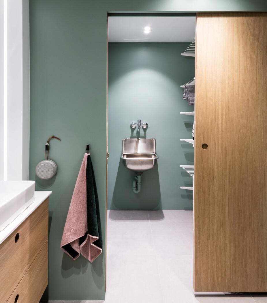 SKYVEDØRER: Vaskerommet kan skjermes av fra badet ved hjelp av doble skyvedører i eik. Løsningen er bygget av møbelsnekker. Fargen på veggene har koden NCS 3010-G10Y.
