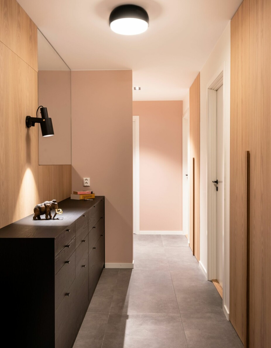 HALVVEGG: Den markerer entréen og sørger for at blikket ikke stanser i døren til toalettet i motsatt ende. Gulvflisene Glocal er fra Mirage, Fagflis. Veggfargen er Deco Pink fra Jotun. En svartbeiset kommode med seksten skuffer sørger for tilstrekkelig oppbevaringsplass, og fungerer dessuten som en slags hylel man kan legge ting på. Vegglampen Volume 2 er fra Rubn, plafonden Over Me er fra Northern.
