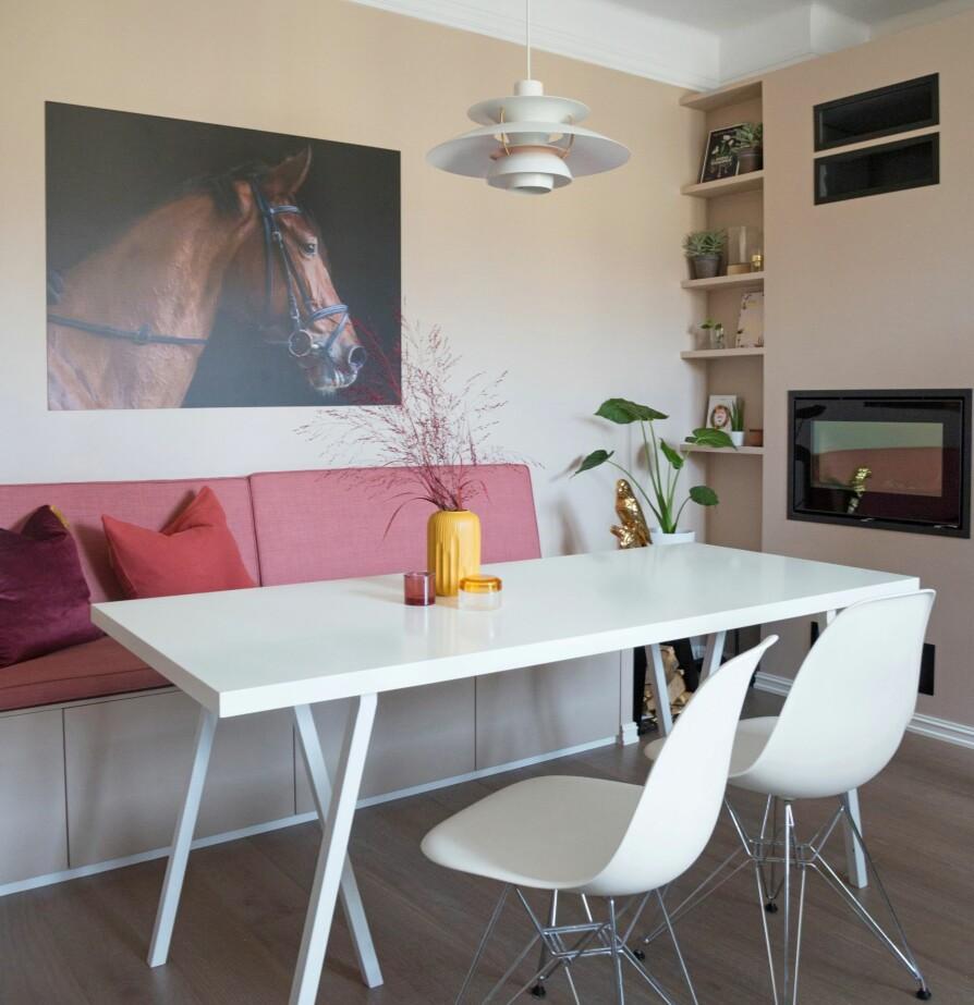 NY SPISESONE: Spisesonen på det nye kjøkkenet er blitt et trivelig hjørne med sofa, peis og integrerte hyller. Sofabenken er laget av kjøkkenskap fra Ikea, mens de rosa putene er sydd på mål hos skredder. Spisebord, stoler og lampe hadde eierne fra før. Bildet på veggen er fra CopyCat.