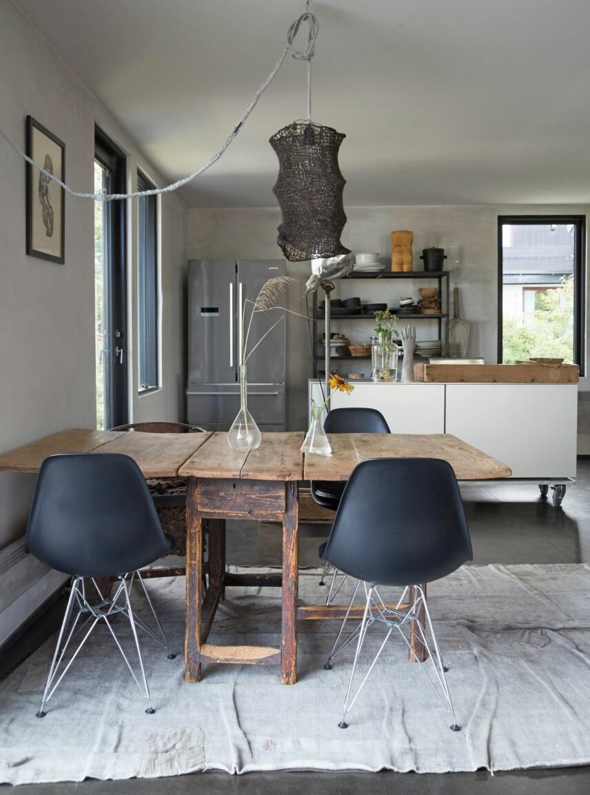 ANTIKT OG DESIGN: Spiseplassen består av et antikt bord og Eames-stoler som er kjøpt brukt. Gulvteppet er fra Private 0204, et dansk firma som redesigner vintagetepper, og bildet på veggen er av Embla Maria Øverbye. Taklampen med strikket skjerm er Vigtel Høllands egen design, som hun også selger på slowdesign.no.