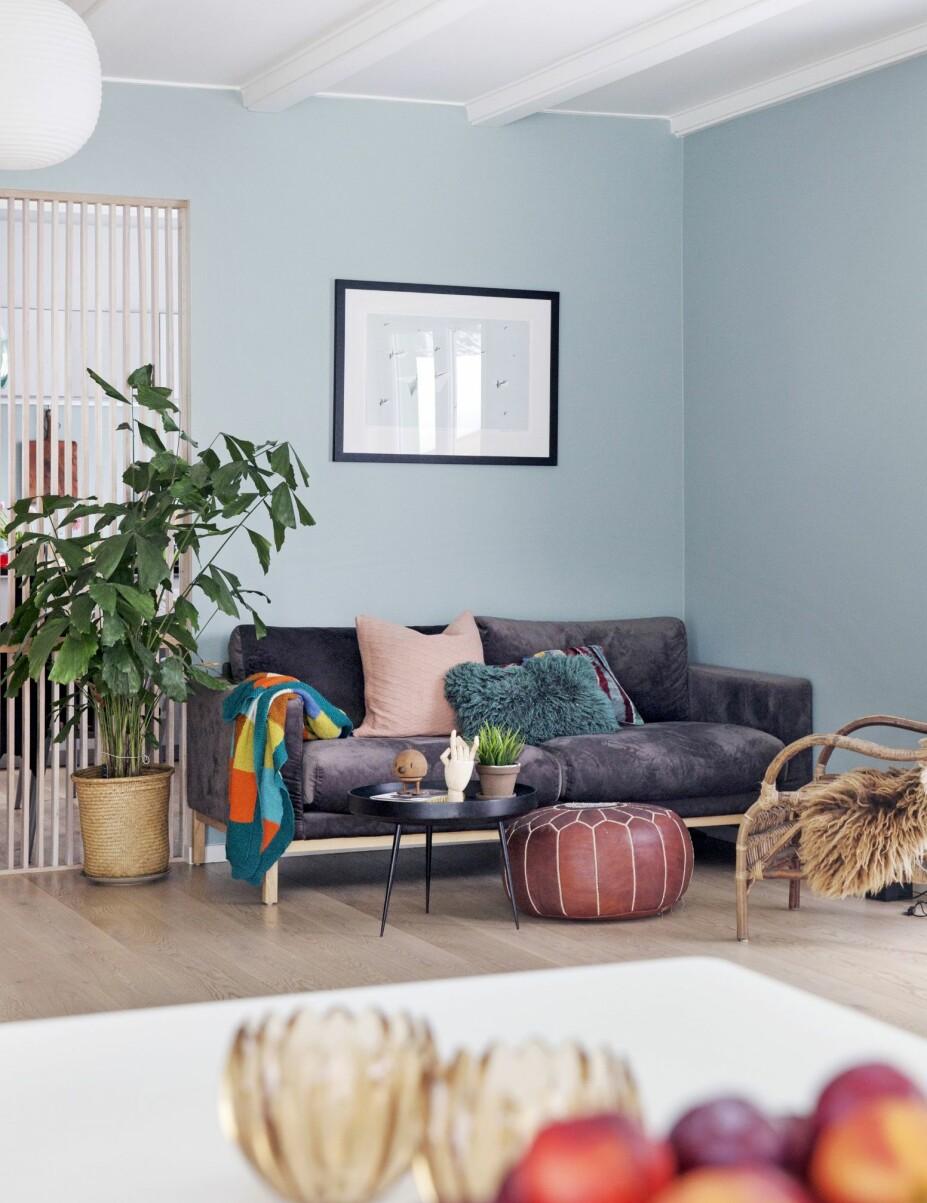 MÅTTE KVITTE SEG MED SOFA: Henriettes «sofa giganticus» måtte vike til fordel for en vanlig treseter, som passet inn i stua i det nye hjemmet. Blåfargen på veggen, som hun beskriver som et kjønnsnøytralt alternativt til rosa, er blandet av kjæresten Rune. Rosa pute fra Anouska, 70-tallsstol fra Ikea, svart bord fra Eske og puffen er fra Åhlens.