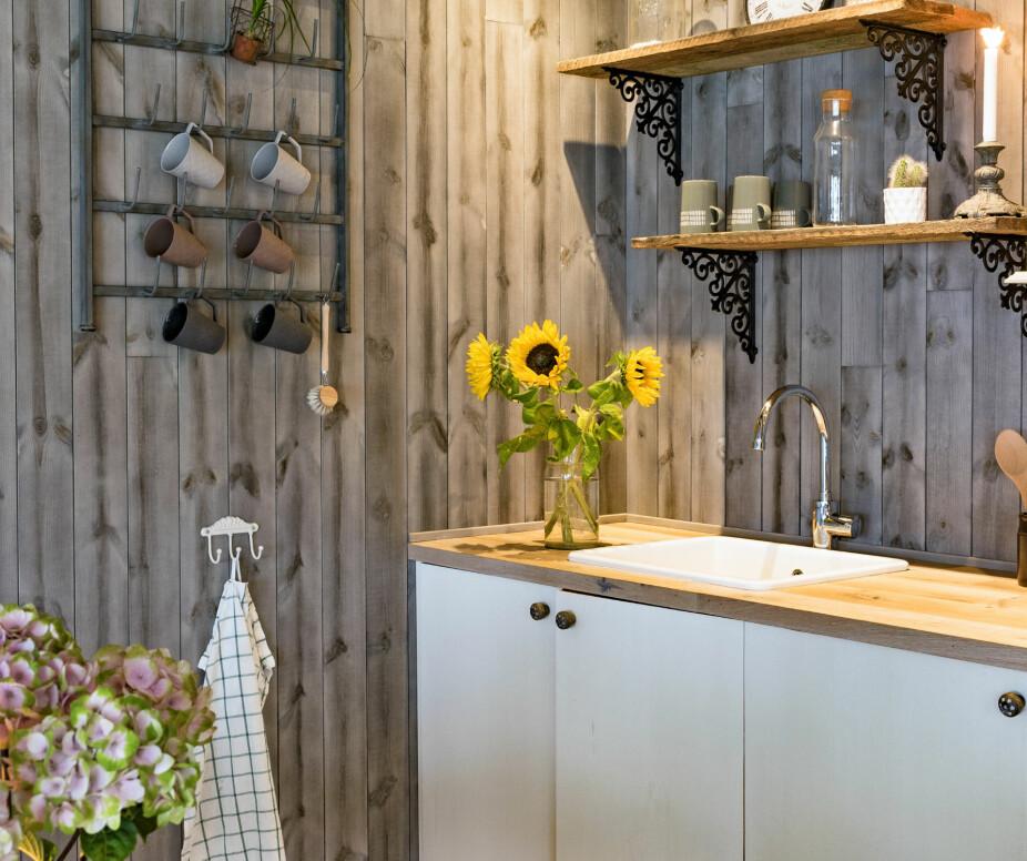 HJEMMELAGET: Kjøkkeninnredningen er hjemmelagd, praktisk og enkelt bygd av plater. Inne i det ene skapet er det et lite kjøleskap.