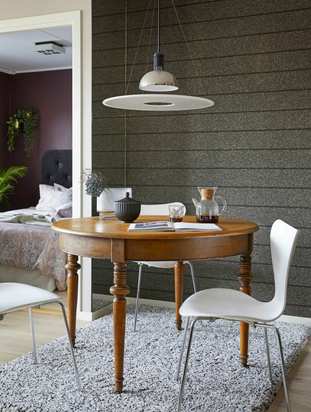 SÆRPREG: Det stripete og matte stentapetet i spisestuesonen tilfører nisjen et spennende særpreg. Tapetet heter Omexco Mica, MCA 7014, og er fra Intag. Spisebordet er et bruktfunn fra finn.no, og stolene er 7-er stoler fra Arne Jacobsen. Taklampen Frisbi er fra Flos, og gulvteppet er fra Ikea.