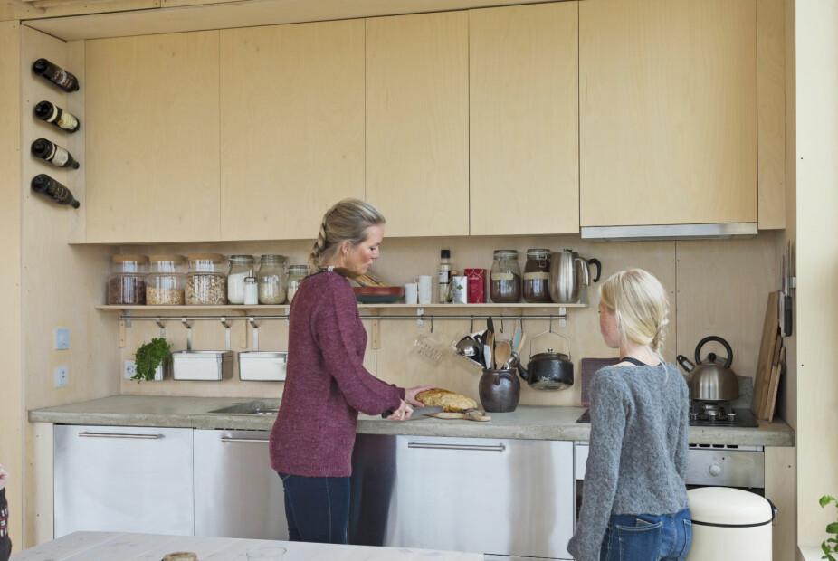 PERSONLIG PREG: Familien har kombinert ferdigkjøpte løsninger med noe hjemmesnekret. Underskap og stålfronter er fra Ikea, mens paret selv har bygget overskapene i bjørkefiner og de åpne hyllene av rundstokker. Benkeplaten i betong er støpt på stedet og mettet for å tåle både varme og vannsprut.