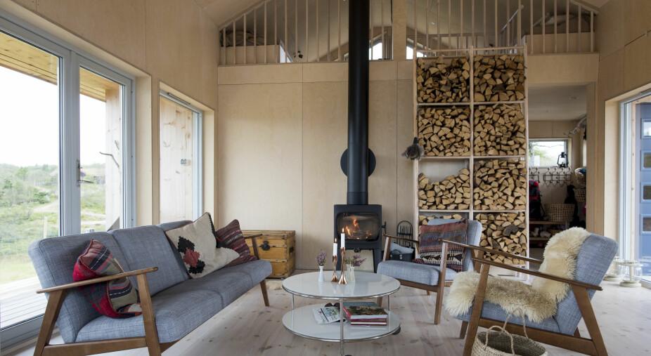 STILRENT: Hytta er enkelt og smakfullt innredet. Paret er opptatt av å skape et hyggelig og lunt miljø, uten å fylle hytta med småting som opptar verdifull plass. To vedovner sørger for varmen i hele hytta. Sofa, stol og bord er fra Ikea, kisten er arvet og vedhyllen har Bård laget selv.
