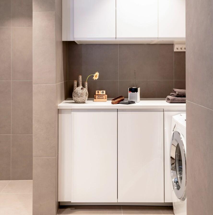 SKAPTE VASKEROM: Det ene hjørnet av badet er innredet som et vaskerom, der man kan få unna klesvask og -bretting i hyggelige omgivelser. Varmtvannstanken Flexi Xpress FX 120 fra Oso er plassert under benken.
