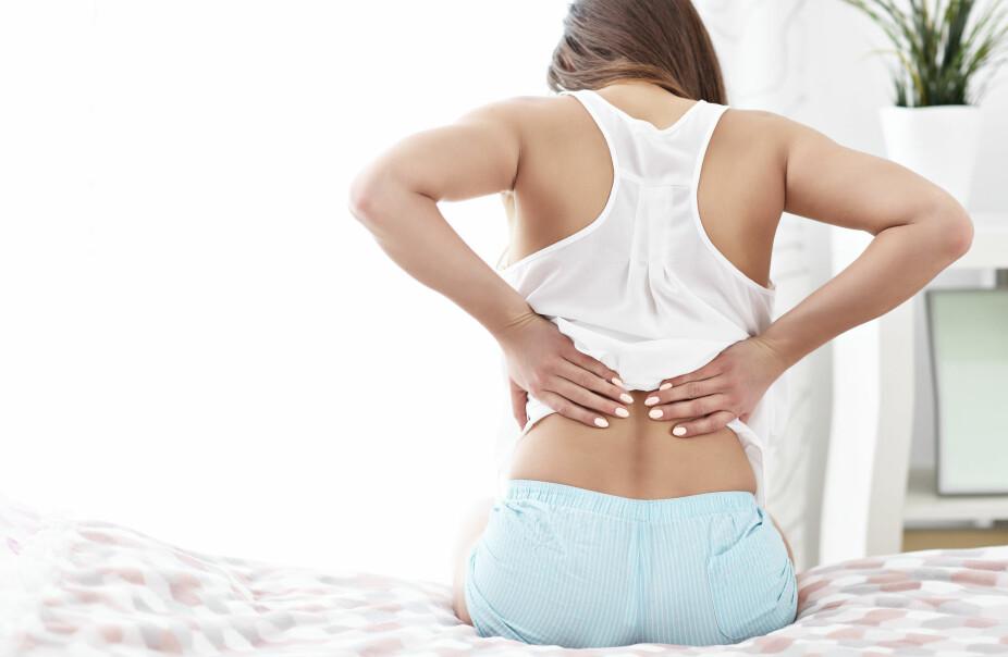 SMERTE: En kvinne med smerter i ryggen holder seg til korsryggen.
