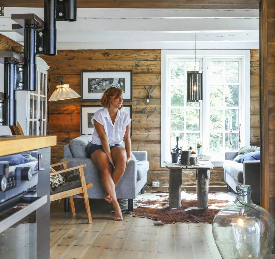 FINE OVERGANGER: Stuen er hyttas eldste del, mens kjøkkenet ble bygget på 60-tallet. Kjøkkenveggen er satt inn med mørk voks, i fargen Antikk eik, for å nærme seg fargen til de originale tømmerveggene i stua.